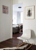 Einblick ins Schlafzimmer mit Polsterbett, im Vorraum steht ein moderner weißer Designer-Schaukelstuhl auf einem Tierfellvorlegen, Fotographien zieren die weißen Wände
