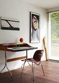 Moderner Schreibtisch mit Stuhl vor weißer Wand mit abstrakten Bildern, im Hintergrund Fenstertür mit Jalousie, davor lehnt ein Kunstobjekt aus Holz an der Wand
