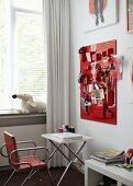 Mädchenhaftes Jugendzimmer mit roter Pinwand zur Aufbewahrung diverser Utensilien, davor ein weißer Klapptisch mit Laptop und einem Metallpolsterstuhl, vor dem Fenster ein weißer Vorhang