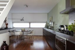 Handle-free kitchen with dark brown, oak fronts and dining area