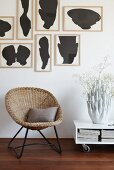Vintage basket chair below artworks by Fons Haagmans and next to low table on castors with coral-shaped vase