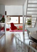 View past white staircase into living room with red designer armchair and designer standard lamp