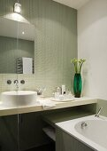 View of washstand and bathtub in bathroom with pistachio green mosaic tiles