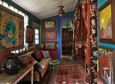 Interior with imaginative artworks on petrol blue walls; sofa opposite niche with draped curtains