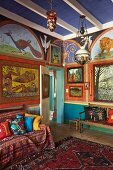 Interior with walls artistically painted with animal motifs, Oriental rug and patterned textiles on sofa