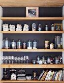Kitchen utensils on shelving in niche with dark back wall