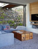Daylight interior in house built into slope with planted gabion wall; vintage wooden trunk used as coffee table for seating area in shades of grey