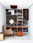 Smart fitted shelving in reading corner with traditional wing-backed chair and foot stool combined with pretty designer lamp