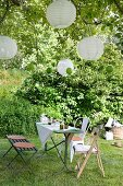 Set table with bench and rustic chairs below lanterns hanging from tree in garden