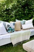 White cushions with patterns and butterfly motifs on bench in garden