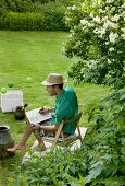 Man wearing summer clothing sitting on chair drawing in garden