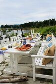 Festively set garden table with robust, white, country-house-style wooden furniture on lakeside terrace