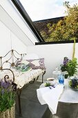 Delicate wire sofa with Oriental cushions, mint plants and hammered metal table in exotic oasis on modern roof terrace