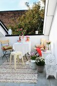 Small seating area with garden furniture, sequinned rug and white, Oriental lantern on modern roof terrace with narrow view