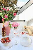 Bouquets of lisianthus and roses in Moroccan ceramic vases decorating table on roof terrace set with dishes of strawberries and crystal glasses