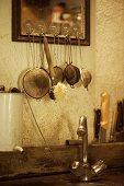 Sieves & washing-up brush hanging above rustic sink