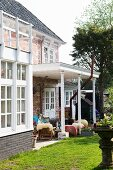 Sheepskins on wooden armchairs on roofed terrace outside traditional brick house