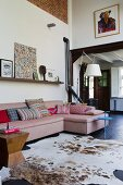 Animal-skin rug and sofa in open-plan interior of renovated country house