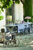 Dining table set with blue tablecloth and flowers on gravel terrace outside French country-house; cushions in pull-along wagon in foreground