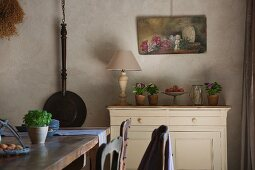 Provençal dining room with cast iron pan and still-life painting on wall; flower arrangements on simple cabinet and rustic wooden table