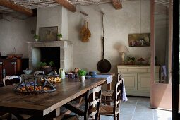 Stylish, rustic dining area in front of masonry fireplace in kitchen of restored Provencal country house