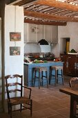 Small, blue-painted breakfast bar in rustic kitchen of Provençal country house