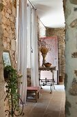 Delicate, French, metal furniture against rustic stone walls in Provençal country house