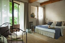 Double bed in rustic, elegant bedroom in French country house