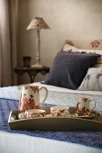 Tea set with toile de jouy pattern on tray on double bed