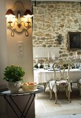 Grand dining table, Baroque chairs and lit candelabras in front of antique painting on rustic stone wall