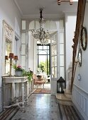 Elegant hallway with Baroque console table, chandelier and staircase with stone treads and wooden balustrade