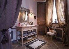 Spacious bathroom with heavy, gathered curtains and long, wooden washstand