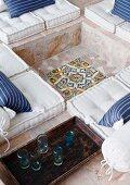Ornamental floor mosaic in footwell of stone-flagged, sunken seating area