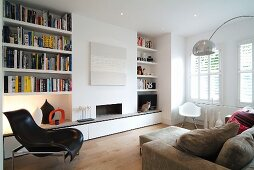 Modern living room with integrated bookcases either side of open fireplace and classic chairs