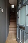 View through open front door into grey-painted stairwell with narrow wooden staircase
