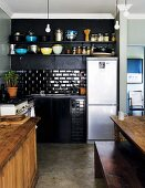 Corner of simple, black kitchen with stainless steel fridge-freezer and partially visible wooden table and bench in traditional setting