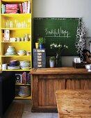 Rustic, half-height cabinet below green chalkboard next to yellow-painted crockery shelves
