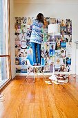Woman, standing on a designer chair, sticks photos on the wall