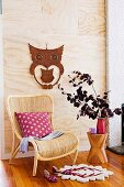 Rattan chair in front of light wooden panel with owl decoration