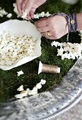 Woman's hands threading popcorn for Christmas tree garlands