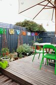 Roof terrace with wooden platform, garden furniture and parasol surrounded by screen and various potted plants