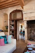 Seating area in front of open fireplace and view into adjoining dining room in old Proven