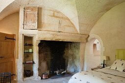 Large open fireplace in Mediterranean bedroom with vaulted ceiling