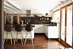 Open-plan, white, designer kitchen with counter, wooden floating shelves and dark parquet floor; terrace doors to one side