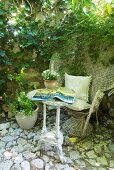 Battered peacock chair in pale wicker on stone floor against climber-covered house facade