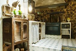Old kitchen furnishings and modern cooker on tiled platform in farmhouse