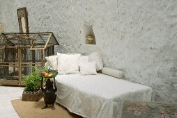 Simply day bed in front of large bird cage on floor in loggia of Mediterranean house