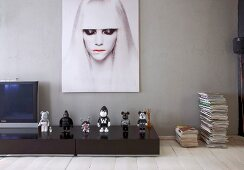 Black and white action figures below modern portrait of woman in Berlin artist's apartment