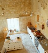 Open-plan kitchen with exposed limestone walls in Château Maignaut (Pyrenees, France)
