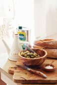 Olives, olive oil, bread, salt & pocket knife on wooden board in kitchen of Château Maignaut (Pyrenees, France)